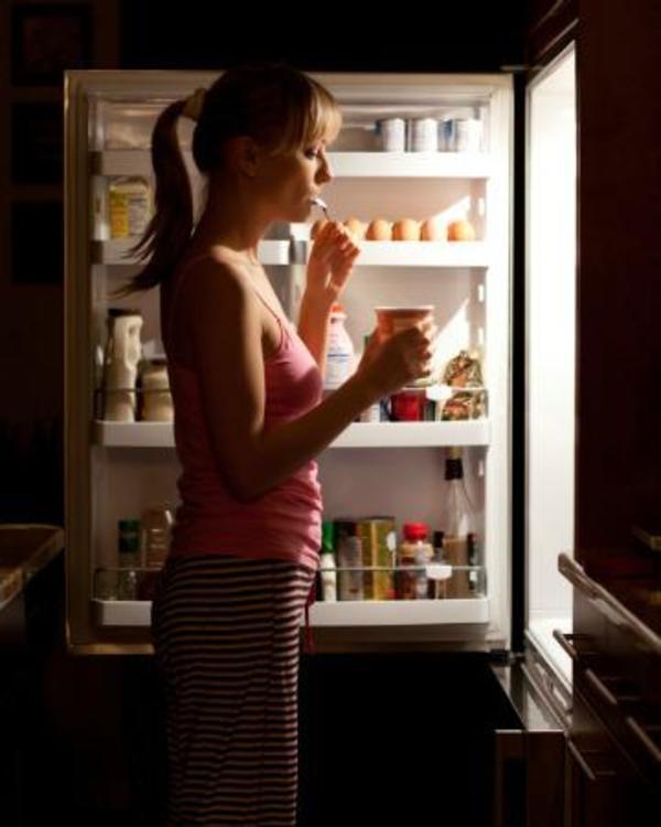 Mulher atacando a geladeira no meio da noite